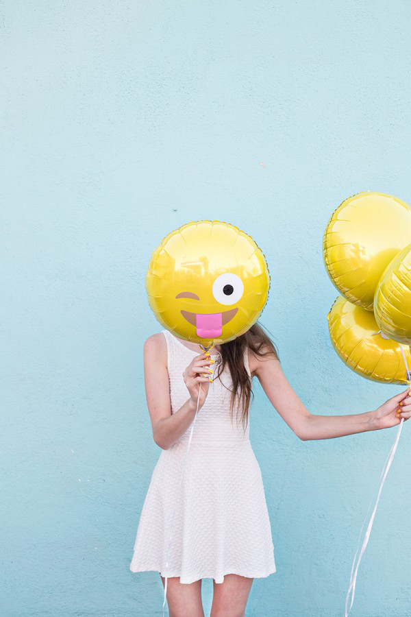 Women Holding Smiling Face Emoji Balloon